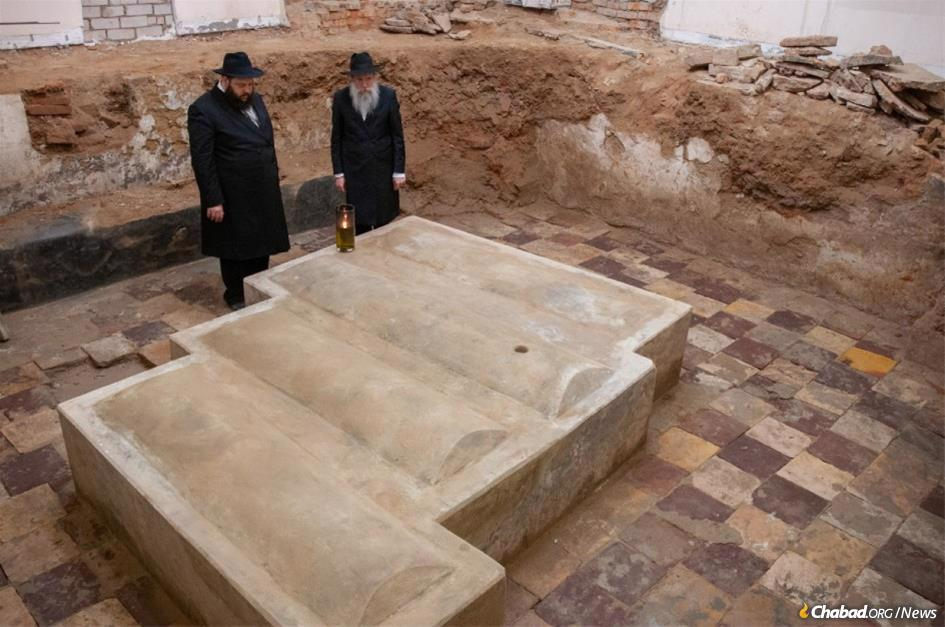 "Rabbi Moshe Thaler (left), rabbi of and Chabad-Lubavitch emissary to Berdichev, Ukraine, stands together with Rabbi Shlomo Wilhelm, director of Chabad of Western Ukraine and rabbi of nearby Zhitomir, at the newly unearthed original mausoleum and gravesite of the great Rabbi Levi Yitzchak of Berdichev (1740-1809), the great ""defender of the Jewish people."" (Photo: Chabad of Berdichev)"