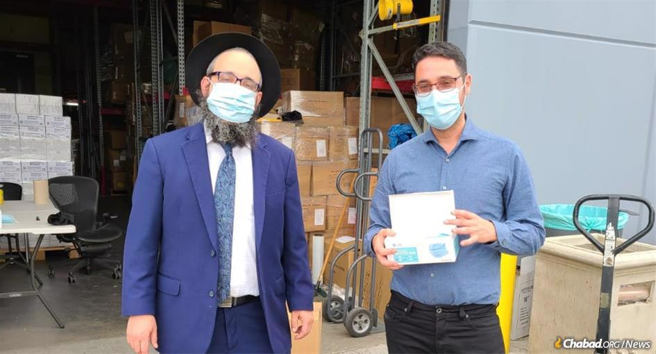 Rabbi Moshe Levin, left, with Yosef Cohen, who with his wife, Alona, have donated 4 million masks to Chabad centers.