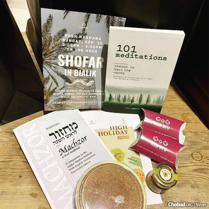 A gift bag from Chabad on the Coast in Tel Aviv includes an invitation to a public shofar-blowing, candles for the holiday, a prayer brochure, inspirational reading, home-baked honey cake and a jar of honey (apple not included).