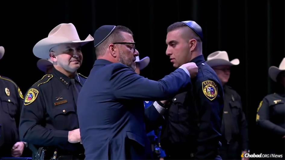 Proudly wearing a kippah, Seth Frydberg was sworn in as the newest deputy sheriff in Bexar County, Texas, with the assistance of his father, Felix Frydberg, center, the son of Holocaust survivors, as Sheriff Javier Salazar, left, looked on.