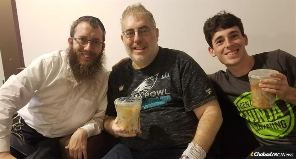 David Ginsberg, center, credits Rabbi Bentzion Butman, left, with saving his life after Ginsberg became desperately ill in Cambodia and the rabbi arranged for a difficult blood transfusion. Etan Ginsberg, right, flew into Phnom Penh from the United States to be with his father. The deli containers they're holding contain soup the rabbi made (one chicken soup for the father and another vegan for the son).