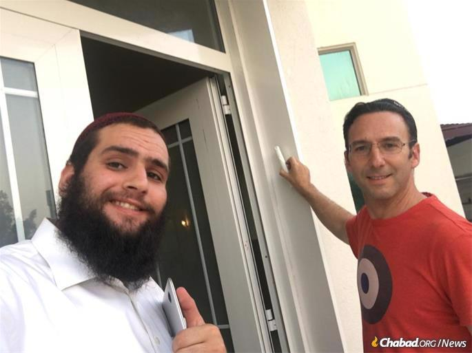 There are three synagogues in the UAE: two in Dubai, and a one in Abu Dhabi. Here Rabbi Duchman assists Ross Kriel with affixing the mezuzah to the Villa Synagogue.