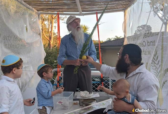 Rodal and children help a local resident do the mitzvah of lulav and estrog.