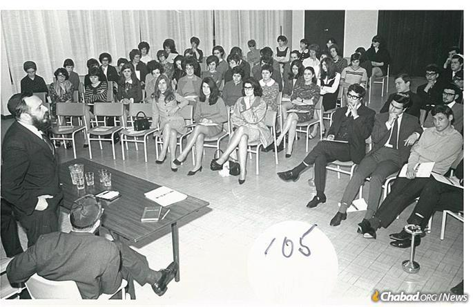 Sacks (front row, second from right, with his hand on his chin) attending a lecture for students by Rabbi Zalman Posner, celebrating the opening of Lubavitch House in London in March 1968.