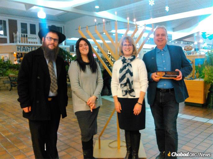 """Rabbi Shmuly and Fraidy Hecht (left), co-directors of Chabad Okanagan in Kelowna, British Columbia, lead a Hanukkah menorah-lighting in Salmon Arm, B.C. (joined by Salmon Arm Mayor Nancy Cooper and City Councillor Tim Lavery), as part of their """"Eight Nights, Eight Sites"""" program. (Credit: Chabad Okanagan)"""
