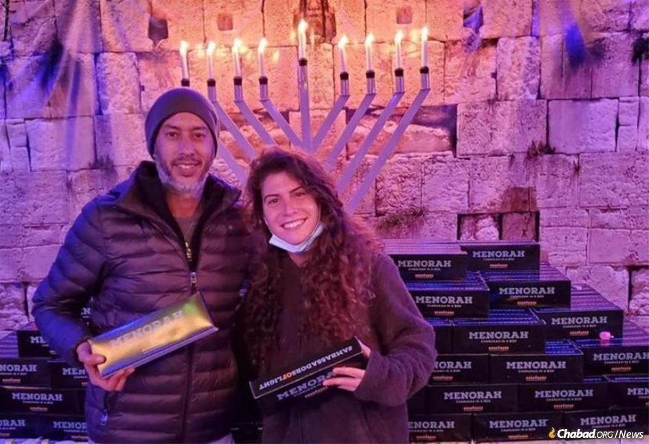 "All around the world, a volunteer army of ""Ambassadors of Light"" like Shai Elmaleh and Danielle Gabi of Pacific Beach, Cal., will be helping people around the world celebrate Hanukkah."