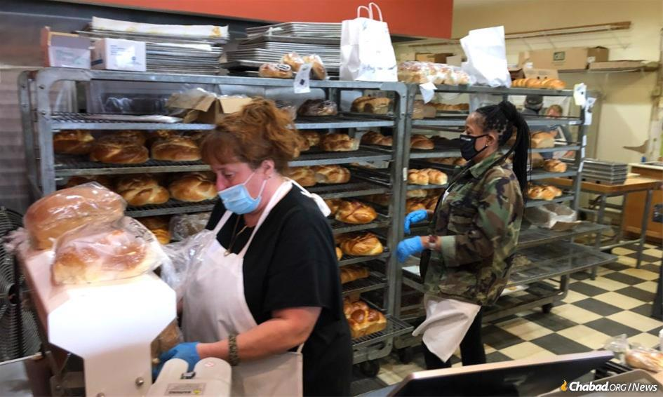 Dakota Bread Company employees serving and slicing fresh-baked loaves of challah
