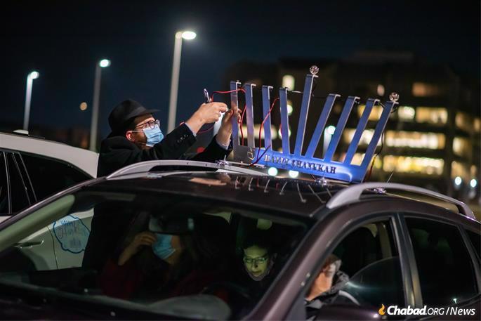 Rabbi Moshe Goldman of Chabad of Waterloo affixes a menorah to the top of his car.