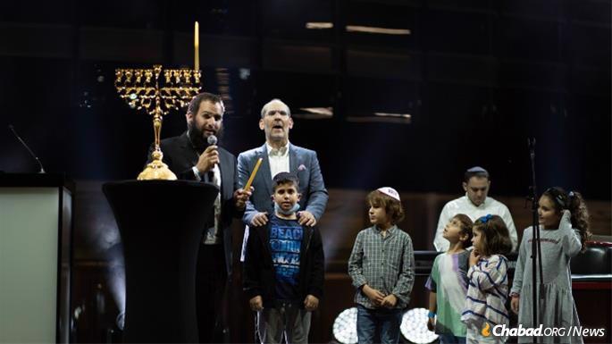 Chaque soir de 'Hanouka, un concert sera organisé. Le premier soir, le Rav Duchman a allumé une petite ménorah, accompagné du chanteur Yishai Lapidot. (Crédit: Yehuda Lavi/CCJ des EAU)