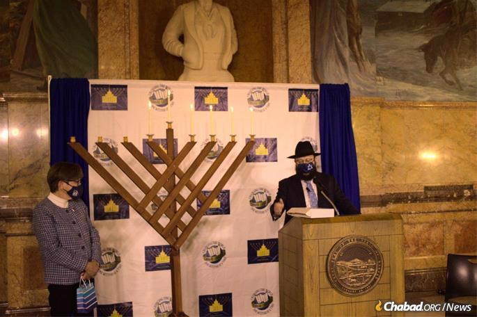 Kansas Gov. Laura Kelly looks on as Rabbi Zalman Tiechtel, who co-directs Chabad at KU with his wife, Nechama Dina, speaks after the lighting of the menorah in the Kansas State Capitol in Topeka. (Credit: Guy Dvoretz)