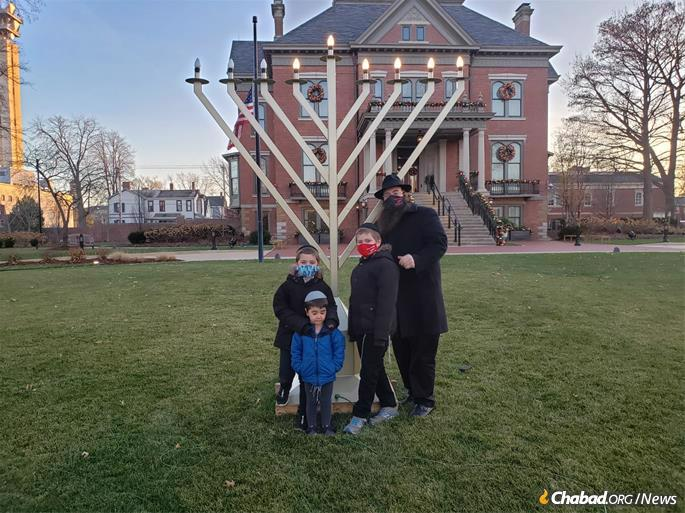Rabbi Chaim Telsner and children light the fifth light of the menorah at the Governor's Mansion in the state capital of Springfield.