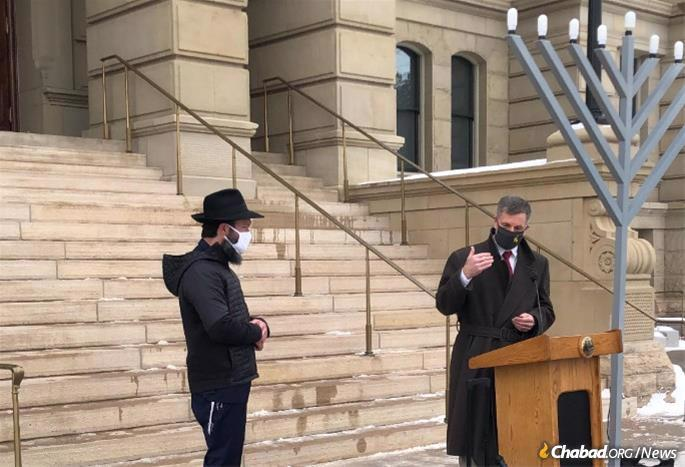 Rabbi Zalman Mendelsohn of Chabad-Lubavitch of Wyoming looks on as Wyoming Governor Mark Gordon speaks during a menorah-lighting ceremony at the Wyoming State Capitol