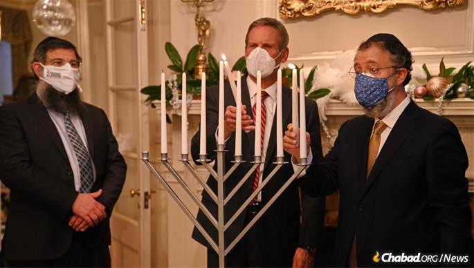 Rabbi Levi Klein, regional director of Chabad of Tennessee (left) and Rabbi Yitzchak Tiechtel of Chabad of Nashville (right) look on as Tennessee Gov. Bill Lee kindles the shammash helper candle during the menorah lighting ceremony at the Tennessee Governor's Mansion.