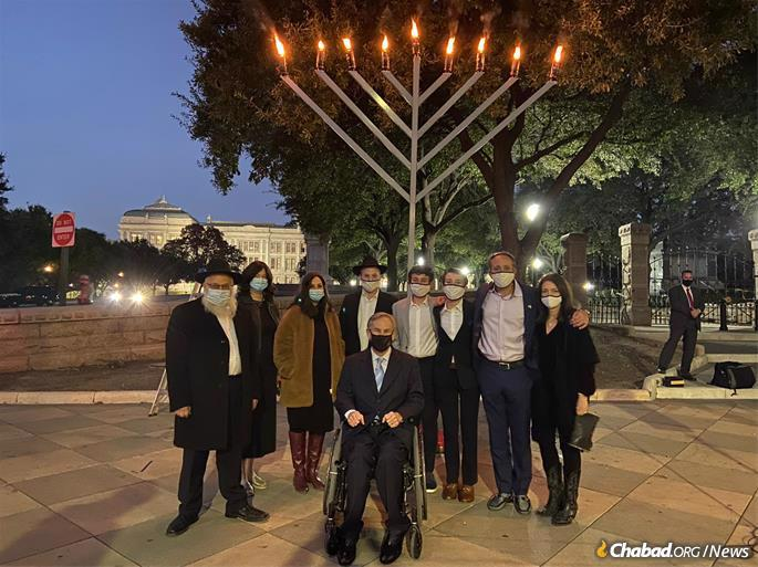 Texas Governor Greg Abbott (center) poses with (from left) Rabbi Yosef Levertov, Rochel Levertov, Mussy Levertov, and Rabbi Mendy Levertov of Chabad of Austin as well as other participants during the menorah-lighting ceremony at the Texas State Capitol.