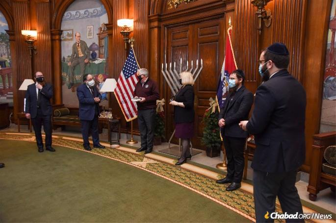 """In advance of Hanukkah and in lieu of the annual menorah-lighting at the Governor's Mansion, a group of Chabad representatives from across the state came to the Governor's Office for a brief visit on Dec. 5. During the quick meet-and-greet, Gov. Mike Parson proclaimed """"the days of December 10-18 as the days of 'Show-Me Chanukah' in Missouri,"""" as has become an annual tradition. From left: Rabbi Avraham Lapine of Columbia, Rabbi Yosef Landa of St. Louis County, Gov. Parson, First Lady Teresa Parson, Rabbi Yossi Abenson of the Central West End and Rabbi Chaim Landa of St. Charles County. (Credit: Julie Smith/Chabad of Greater St. Louis)"""