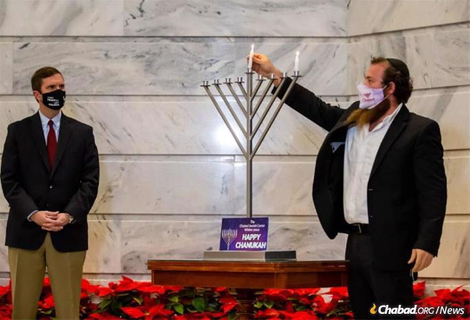 Kentucky Governor Andy Beshear looks on as Chabad-Lubavitch Rabbi Chaim Litvin of Chabad of Kentucky lights the menorah at the State Capitol in Frankfort, Kentucky.