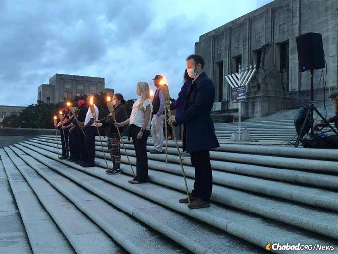 Eight health-care heroes and frontline workers are honored to hold torches and help light the menorah at the Louisiana State Capitol, placed by Chabad serving LSU & Greater Baton Rouge. (Credit: Chabad serving LSU & Greater Baton Rouge)