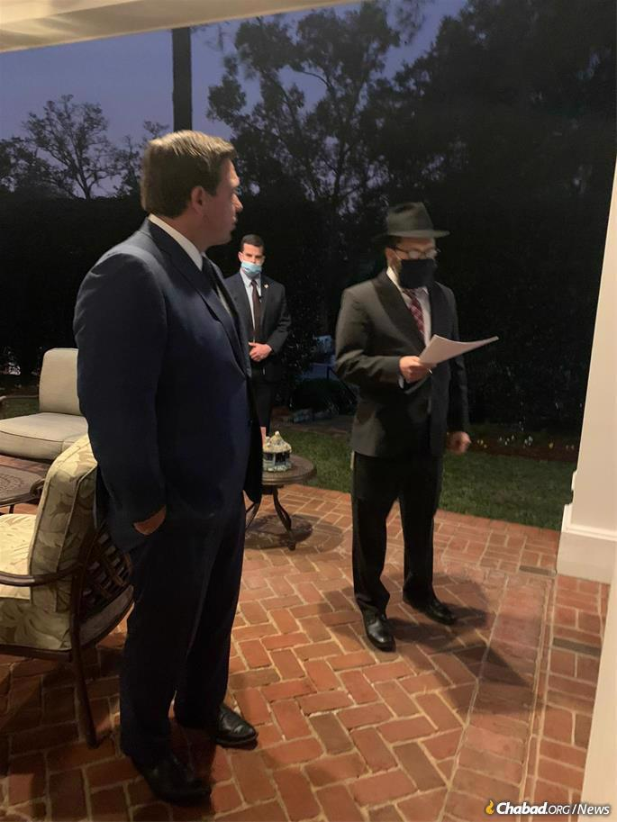Florida Gov. Ron DeSantis looks on as Chabad-Lubavitch Rabbi Schneur Zalman Oirechman, who co-directs Chabad Lubavitch of the Panhandle-Tallahassee, speaks during a menorah-lighting ceremony at the Governor's Residence in Tallahassee.