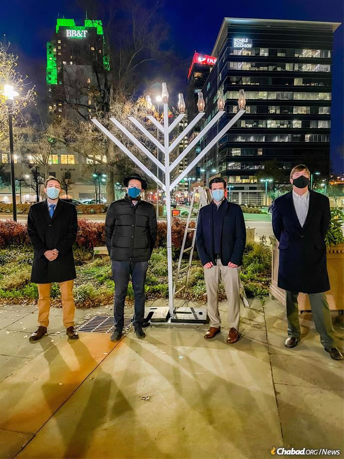 Jewish community leaders stand in front of a menorah lit on Downtown Raleigh's historic Fayetteville Street down the block from the North Carolina State Capitol. From left: Bill King, CEO of Downtown Raleigh Alliance; Rabbi Zalmy Dubinsky, who co-directs Chabad Young Professionals Raleigh with his wife, Mushky; Dr. Josh Dloomy, a Jewish health-care hero who was honored with the menorah-lighting; and City Councilman David Knight.