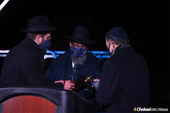 """From right: Gov. Gary R. Herbert, Rabbi Benny Zippel, Executive director of Chabad Lubavitch of Utah and Rabbi Avremi Zippel, Program Director of Chabad Lubavitch of Utah, kindle the shammash used to light the menorah at """"A Utah Chanukah Celebration"""" on the grounds of the Utah State Capitol. (Credit: Melissa Majchzrak for Chabad of Utah)"""