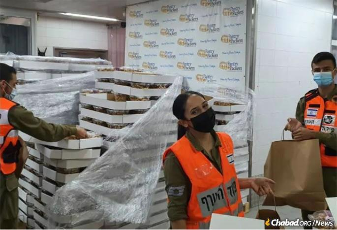 Israeli soldiers volunteer to pack and deliver food to the needy at Colel Chabad's Pantry Packers.