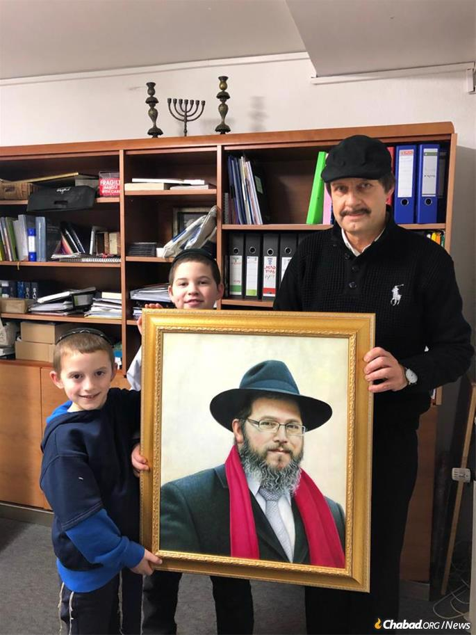 A member of the Hanover Jewish community presents two of the Wolff children with a portrait of their father, Rabbi Binyamin Wolff. Each year at Hanukkah, Rabbi Wolff would give red scarves to community members as a gift.