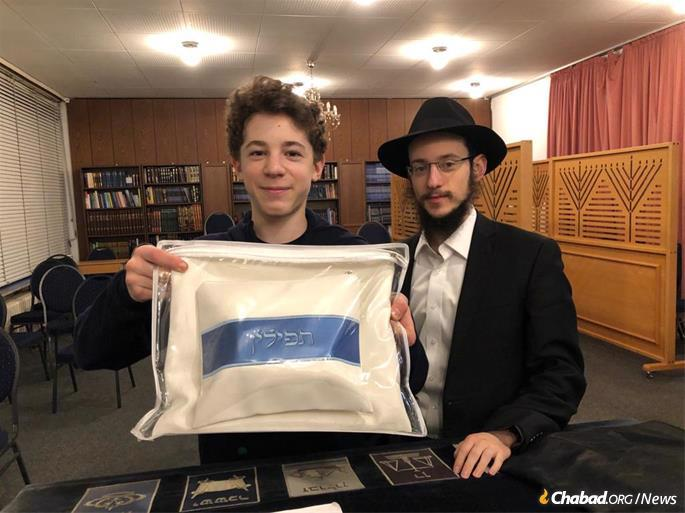 David Reginer is presented with a new set of tefillin by Rabbi Levi Gotlieb. Rabbi Wolff had arranged for David to have a brit milah a few years ago, and the young man chose to celebrate a belated bar mitzvah this year. The tefillin were donated by the Council of European Rabbis in Rabbi Wolff's memory.
