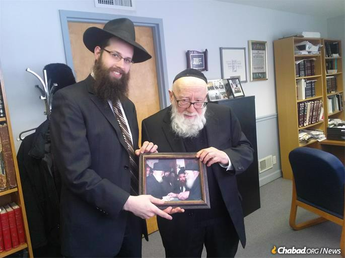 Rabbi Meir Moscowitz presents Rabbi Schwartz with a photo of his receiving a dollar and a blessing from the Rebbe.