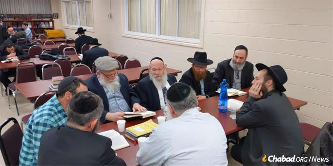 A group of men meet to study the weekly sichah with Rabbi Moshe Spalter.