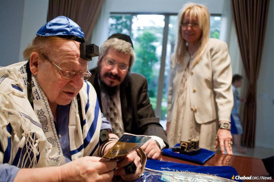 "Sheldon Adelson prays with Rabbi Shea Harlig, director of Chabad of Southern Nevada, while his wife, Dr. Miriam Adelson, looks on proudly. Photo credit: Marc Asnin for ""A Light Unto the Nations,"" a photo book project looking at Chabad's work around the world."