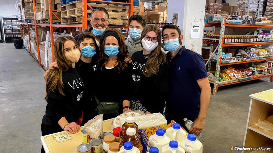 "Volunteers at ""The Family Store,"" a massive, fully-stocked grocery that provides subsidized basic food items and household staples to customers, and which has been a key resource in Montreal during the coronavirus pandemic."