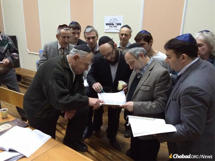Rabbi Shneur Zalman Schneersohn, center, reviews old maps of the city with members of the Rovno Jewish community.