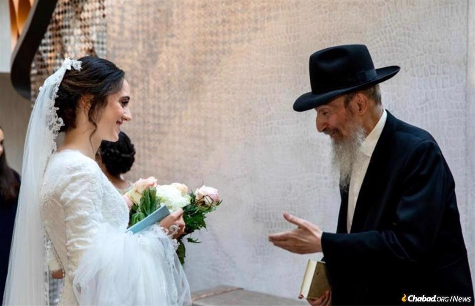 Rabbi Elie Cohen with granddaughter Bassie Weitman at her wedding.