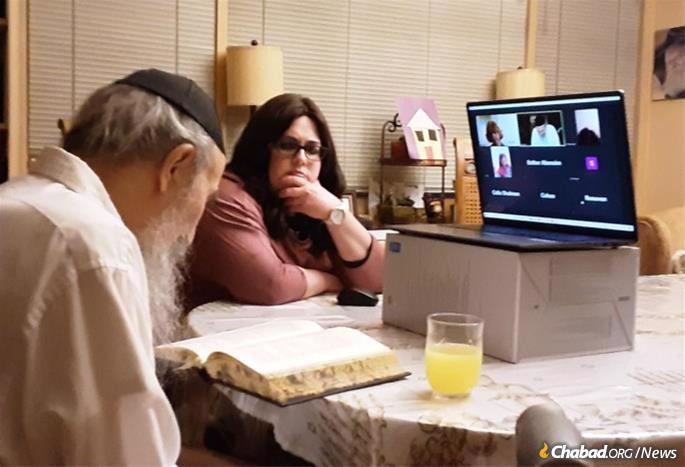 Soon after returning home after months in the hospital battling the coronavirus, Rabbi Cohen gave a Zoom class as his daughter-in-law Rochie Cohen looks on.