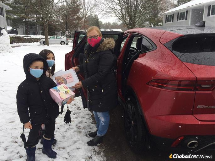 Adrianne Hanley delivers Purim packages to Boston-area Jewish residents with the help of the rabbi and two of the Lezell children, Shterna Sarah, 7, and Sholom, 5, who is carrying a box of matzah for one recipient, a nearly 90-year-old English professor.