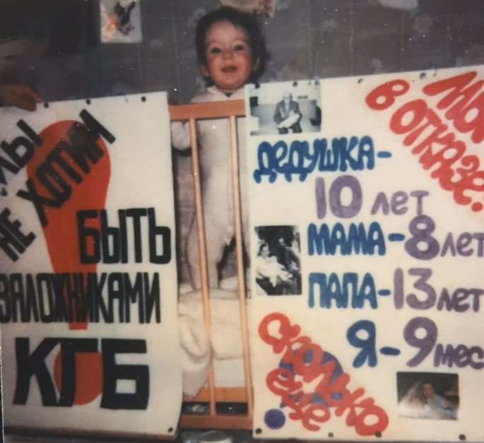 Aliyah, 9 months old, with two posters the evening before a demonstration.