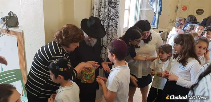 Rabbi and Rebbetzin Garelik distributing candy to students of the Chabad day school in Milan, Italy.