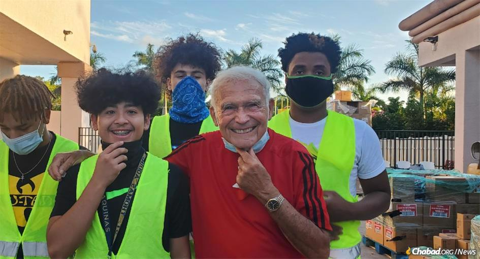 Ivan Gluck (pictured with fellow volunteers), an 82-year-old child Holocaust survivor, is among the first to show up each week at Chabad of Coral Springs' drive-by food distribution in South Florida.