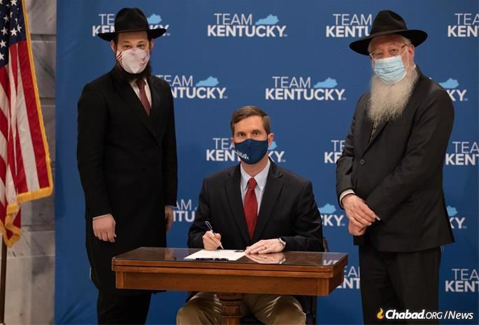 Kentucky Gov. Andy Beshear signs the proclamation designating March 24, 2021 as Education and Sharing Day in the state of Kentucky as Rabbi Avrohom Litvin (right), who directs Chabad of Kentucky, and Rabbi Shlomo Litvin (left), who directs Chabad of the Bluegrass in Lexington, Ky., look on. (Credit: Scottie Ellis)