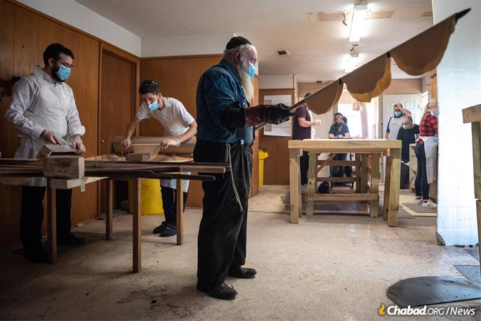 """From there the baker (a """"zetser"""" in Yiddish) at the Texas Shmurah Matzah Bakery in Fort Worth, Texas, places the matzahs into the 1,300-degree oven, on Monday, March 15, 2021. (Photo: Ben Torres for Chabad.org)"""
