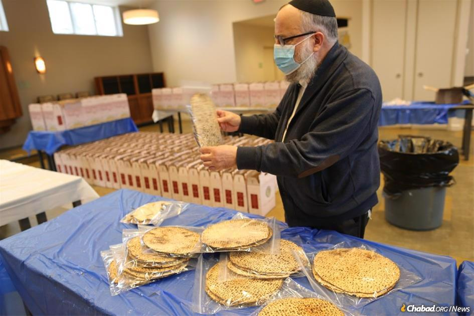 Rabbi Yosef Landa, regional director of Chabad of Greater St. Louis, packs shmurah matzah to be distributed. More than 4,000 people in St. Louis will receive a Passover Seder-to-Go kit, part of the global Passover campaign launched in 1954 by the Rebbe. An estimated 4 million hand-baked shmurah matzahs will be distributed by the Chabad-Lubavitch movement leading up to Passover. (Credit: Bill Motchan)