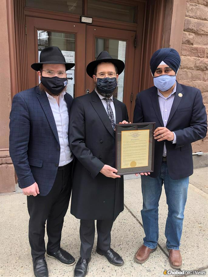 Mayor of Hoboken, N.J. Ravi Bhalla (right) presents the proclamation dedicating March 24, 2021, as Education and Sharing Day in Hoboken to Rabbi Moshe Schapiro (center) and Rabbi Shmuely Levitin (left) of Chabad of Hoboken and Jersey City.