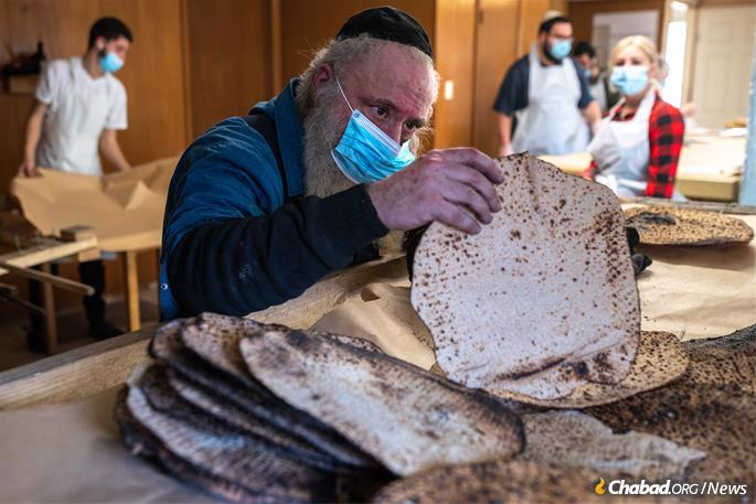 Each matzah at the Texas Shmurah Matzah Bakery in Fort Worth, Texas, is checked to make sure that no dough remains underbaked and thus unsuitable for Passover consumption, seen here on Monday, March 15, 2021. (Photo: Ben Torres for Chabad.org)