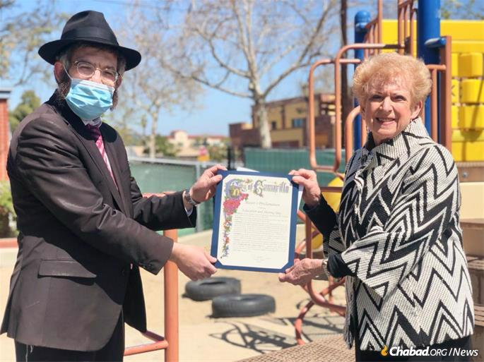 Charlotte Craven, the mayor of Camarillo, Calif., poses with Rabbi Aryeh Lang, who directs Chabad of Camarillo, at an Education and Sharing Day 2021 proclamation ceremony on the grounds of Gan Camarillo, a local preschool under the auspices of the Chabad center.