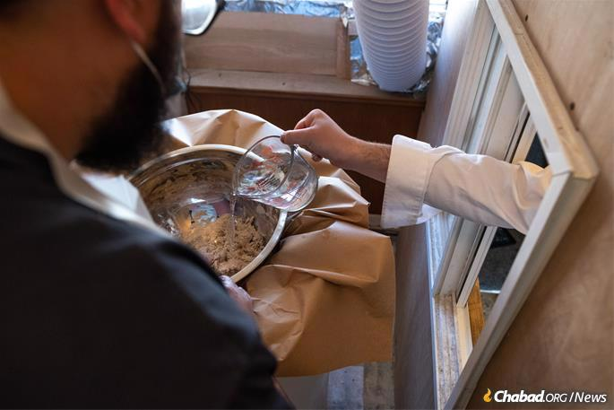 Water and flour are mixed by hand at Chabad's Texas Shmurah Matzah Bakery in Fort Worth, Texas, on Monday, March 15, 2021. The entire matzah-baking process is done by hand from beginning to end. (Photo: Ben Torres for Chabad.org)
