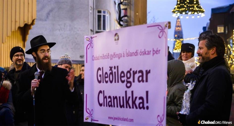Rabbi Avi Feldman speaks at the giant menorah-lighting ceremony in central Reykjavik, Iceland, as the capital's Mayor Dagur Bergþóruson Eggertsson, right, looks on