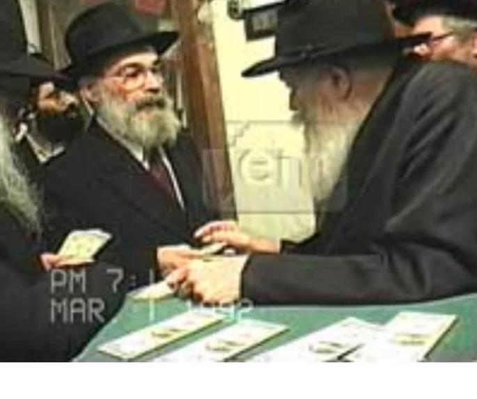 Iser Kirszenberg recibe del Rebe tres billetes de un dólar y una bendición para larga vida.