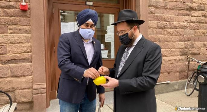 Ravi Bhalla, mayor of Hoboken, N.J., joins Rabbi Moshe Schapiro of Chabad of Hoboken and Jersey City in placing coins in a charity box known as the ARK on Education and Sharing Day in Hoboken, N.J.