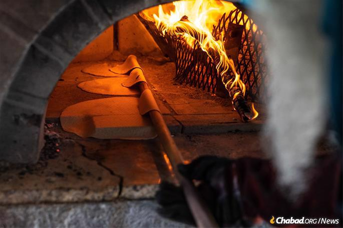 The firewood embers in the matzah oven at the Texas Shmurah Matzah Bakery in Fort, Worth, Texas, never go out and are stoked early each morning in order that it hits the 1,300 degrees required to bake matzah, seen on Monday, March 15, 2021. (Photo: Ben Torres for Chabad.org)