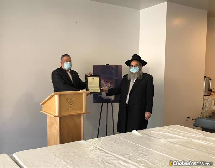 Richard David, the mayor of Binghamton, N.Y., presents the city's Education and Sharing Day proclamation to Rabbi Aaron Slonim, executive director of Chabad of Binghamton. (Credit: Megan J. Brockett)
